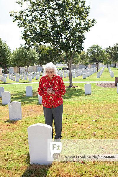 Ältere Frau steht neben Grabstein auf dem Friedhof