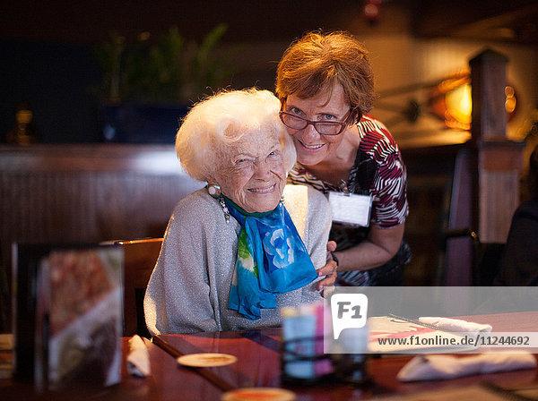 Ältere Frau sitzt am Restauranttisch  reife Frau umarmt sie