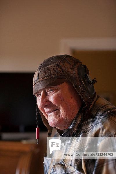 Älterer Mann in der Halle  mit altem Leder-Fußballhelm