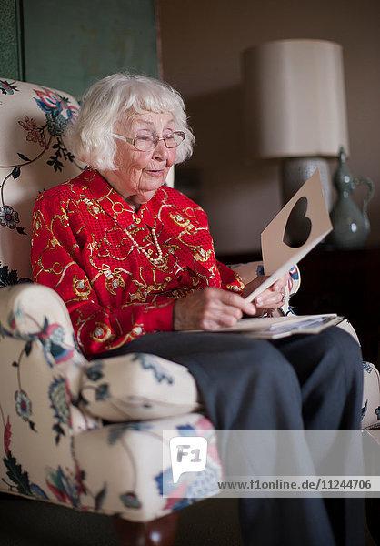 Ältere Frau sitzt auf einem Stuhl und schaut auf eine Grußkarte