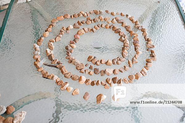 Kleiner Stein in spiralförmiger Anordnung auf Glasplatte