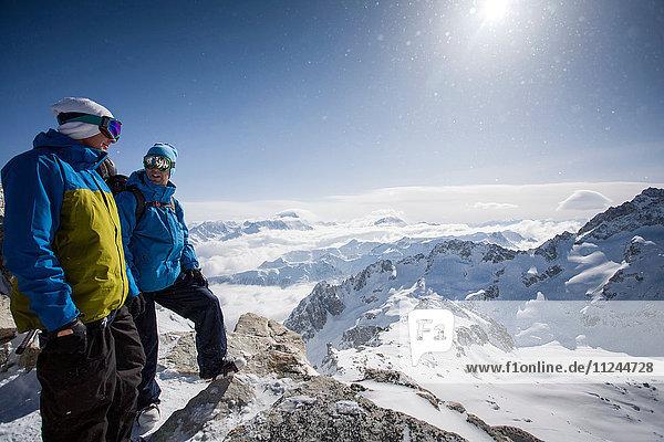 Zwei männliche Snowboarder mit Blick auf die schneebedeckte Landschaft  Trient  Schweizer Alpen  Schweiz