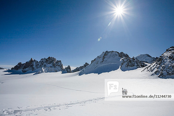 Four male snowboarders hiking across snow-covered landscape  Trient  Swiss Alps  Switzerland