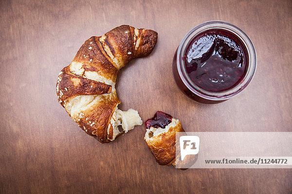 Gebrochenes Croissant auf Holztisch mit Marmelade