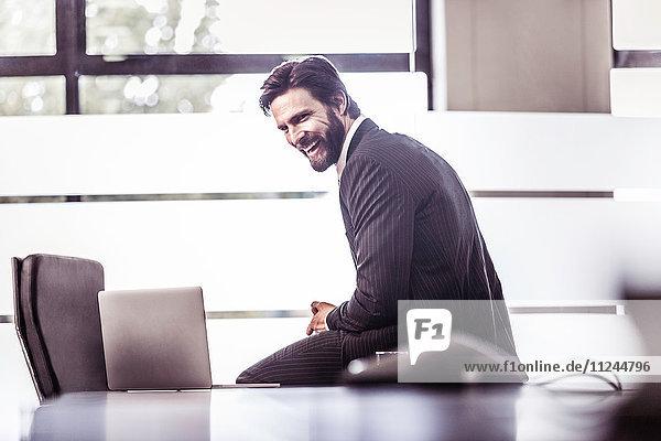 Geschäftsmann sitzt lachend am Tisch im Sitzungssaal