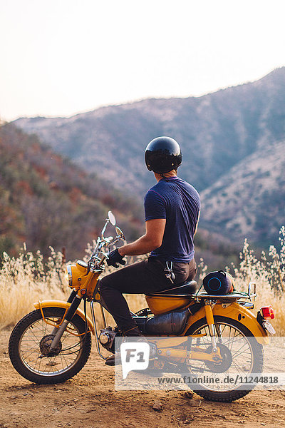 Man sitting on motorbike  looking at view  rear view  Sequoia National Park  California  USA