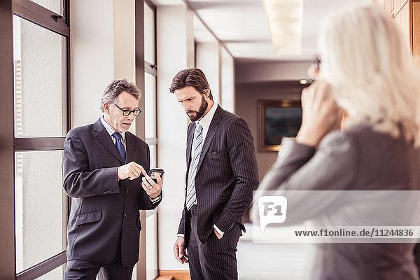 Businesswomen reading smartphone update in office corridor