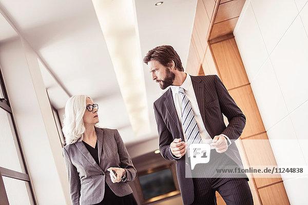 Geschäftsmann und -frau gehen und sprechen im Bürokorridor