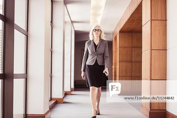 Geschäftsfrau geht den Bürokorridor entlang