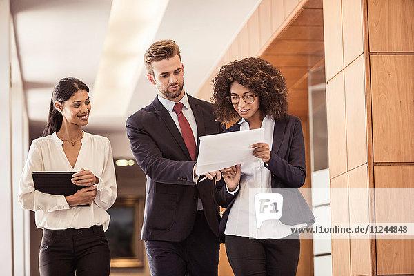 Junge Geschäftsfrauen und Geschäftsmänner gehen und lesen Papierkram im Bürokorridor