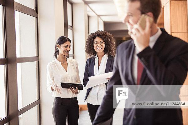 Junge Geschäftsfrauen und Geschäftsmänner im Bürokorridor