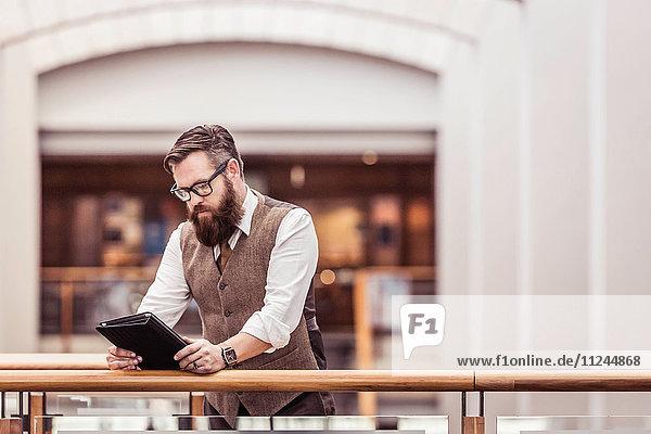 Bärtiger Geschäftsmann mit Tweed-Weste liest digitales Tablett auf Bürobalkon