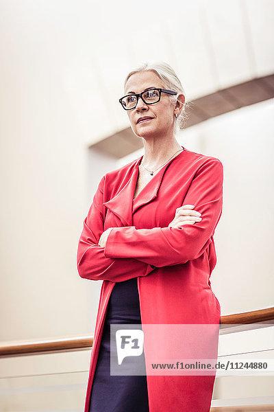 Porträt einer Geschäftsfrau mit verschränkten Armen auf Bürobalkon