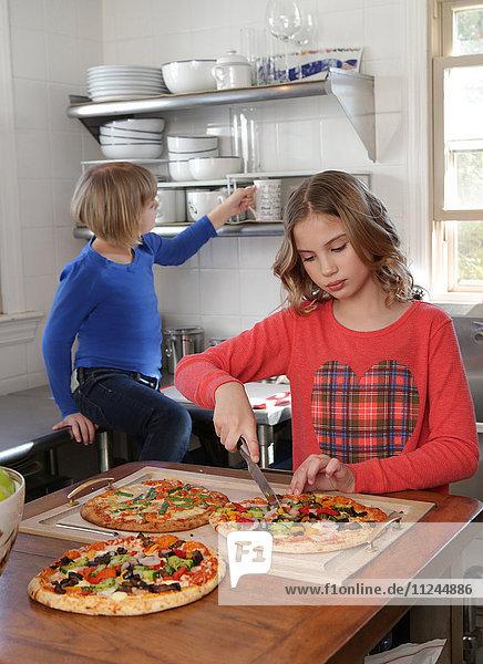 Zwei junge Mädchen in der Küche beim Pizzaschneiden