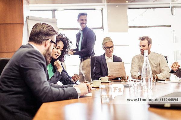 Geschäftsfrauen und -männer diskutieren Ideen bei der Präsentation am Konferenztisch