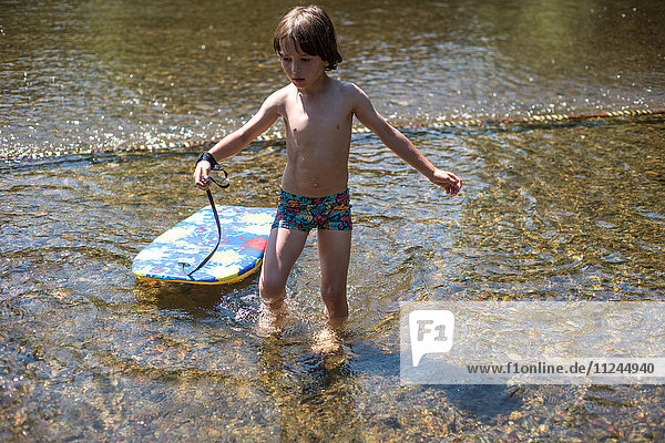 Boy ankle deep in water with body board