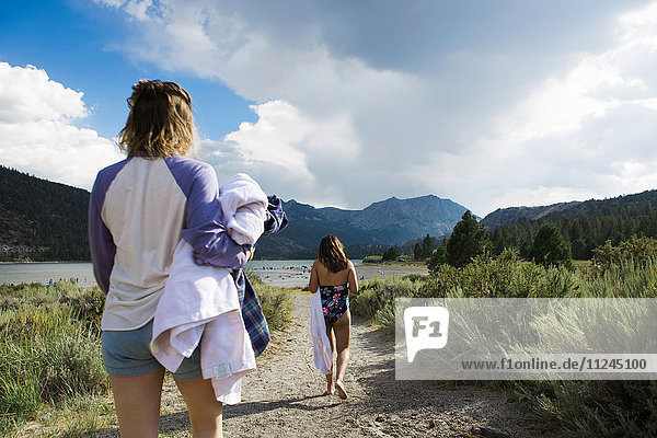 Rear view of two young women strolling to lake carrying towels  Mammoth Lakes  California  USA