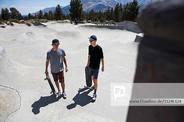 Zwei junge männliche Skateboarder unterhalten sich im Skatepark  Mammoth Lakes  Kalifornien  USA