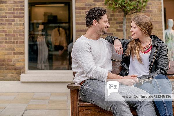 Romantisches junges Paar auf Bank sitzend  Kings Road  London  UK