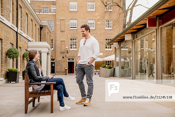 Junger Mann begrüsst Freundin auf Bank sitzend  Kings Road  London  UK