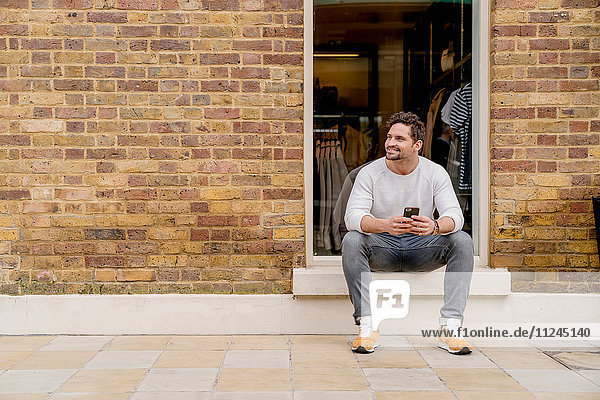 Young man with smartphone sitting on doorstep  Kings Road  London  UK