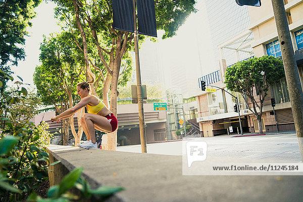 Junge Frau  die im Freien trainiert und gegen eine Wand springt