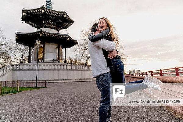Glücklicher junger Mann umarmt Freundin im Battersea Park  London  Großbritannien