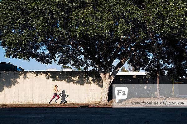 Junge Frau  die sich im Freien bewegt und entlang der Straße läuft