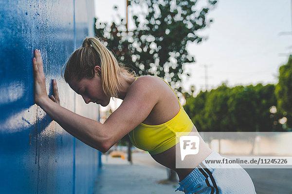 Junge Frau im Freien  die sich gegen die Wand streckt
