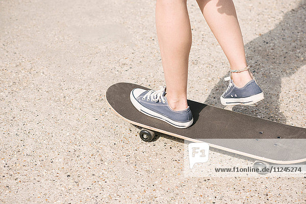 Legs of young female skateboarder skateboarding