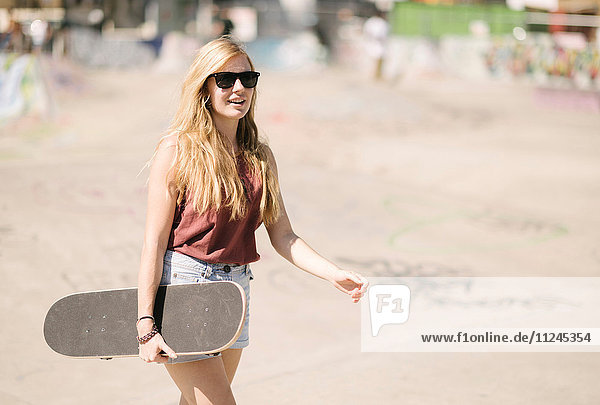 Young woman walking with skateboard in skatepark