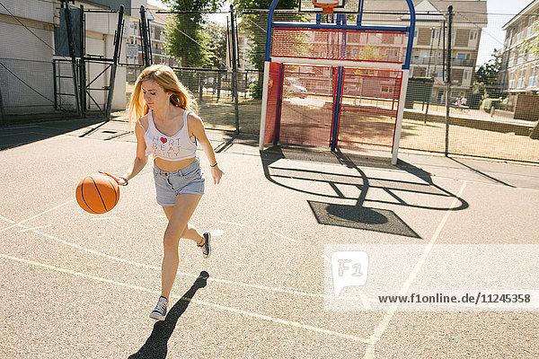 Junge Frau läuft mit Ball auf Basketballfeld
