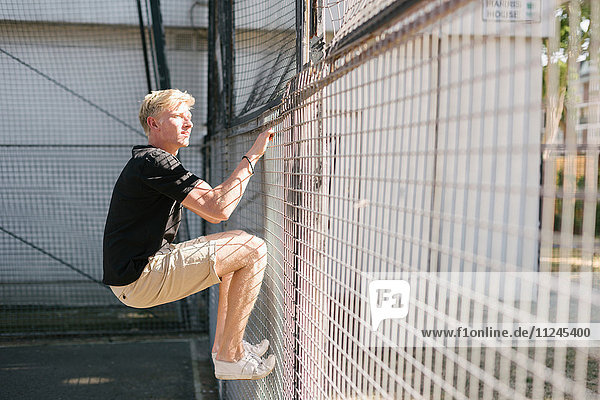 Young man climbing wire fence