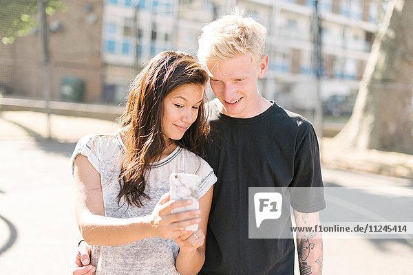 Frau und Freund lesen Smartphone-Update auf dem Basketballplatz