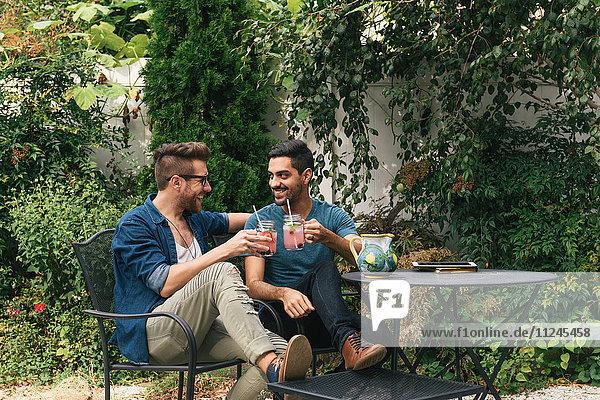 Junges männliches Paar sitzt im Garten und stoßt mit einem Cocktail an