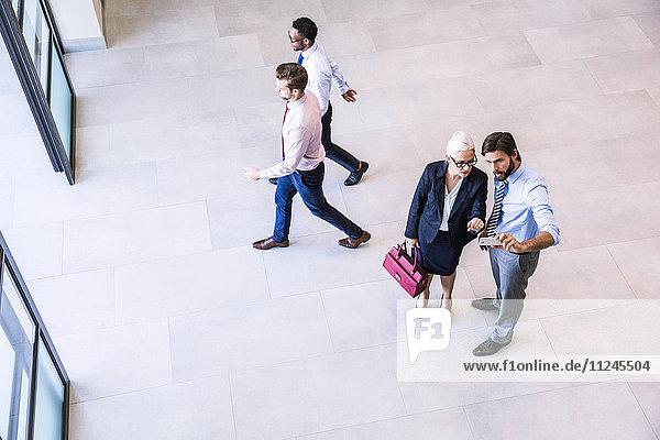 Hochwinkelansicht von zwei Geschäftsleuten  die im Atrium des Büros Smartphone-Text lesen
