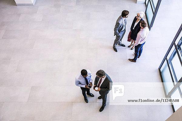 Blick von oben auf Geschäftsfrau und Geschäftsleute  die im Atrium des Büros diskutieren
