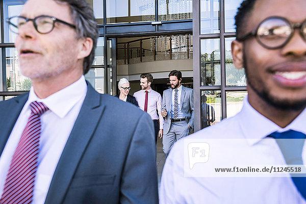 Nahaufnahme von Geschäftsleuten  die das Bürogebäude verlassen