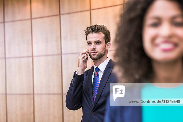 Junger Geschäftsmann spricht mit Smartphone im Büro