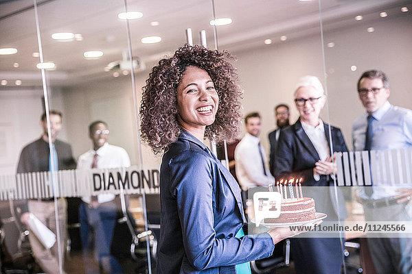 Porträt einer jungen Geschäftsfrau  die einen Festtagskuchen in den Sitzungssaal trägt