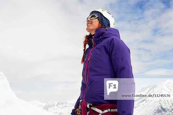 Frau auf schneebedecktem Berg schaut lächelnd auf  Saas Fee  Schweiz