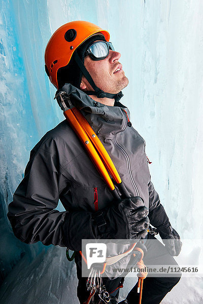 Porträt eines Eiskletterers in einer Eishöhle mit Blick nach oben