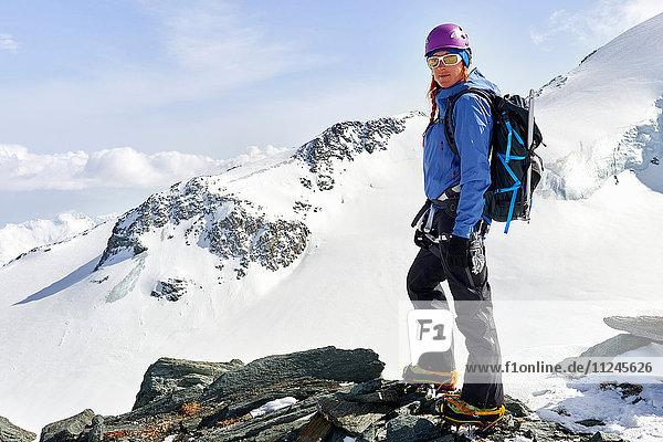 Frau steht auf dem Gipfel eines schneebedeckten Berges  Saas Fee  Schweiz