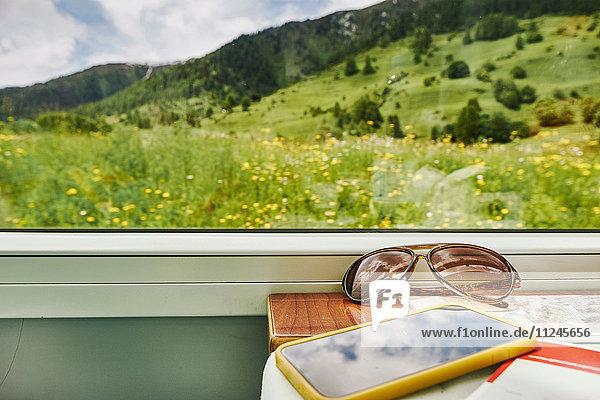 Sonnenbrille und Smartphone am Fenster des Personenzuges  Chur  Schweiz