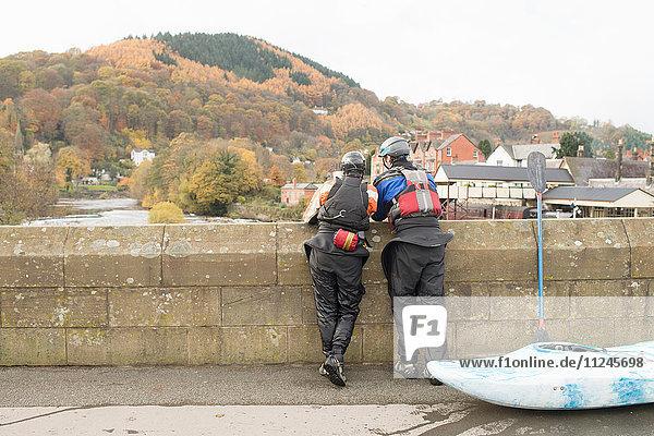 Rückansicht von zwei Kajakfahrern  die von der Brücke auf dem River Dee hinausblicken  Llangollen  Nordwales