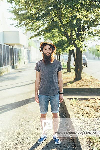 Porträt eines jungen männlichen Hipsters mit Strohhut auf dem Bürgersteig