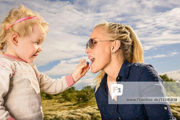Junges Mädchen füttert Mutter Blaubeere