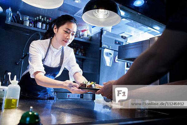Chefkoch überreicht dem Kellner zubereitete Mahlzeit