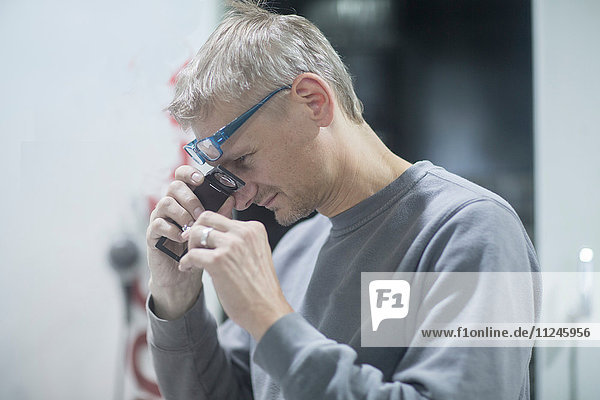 Man looking into magnifying loupe