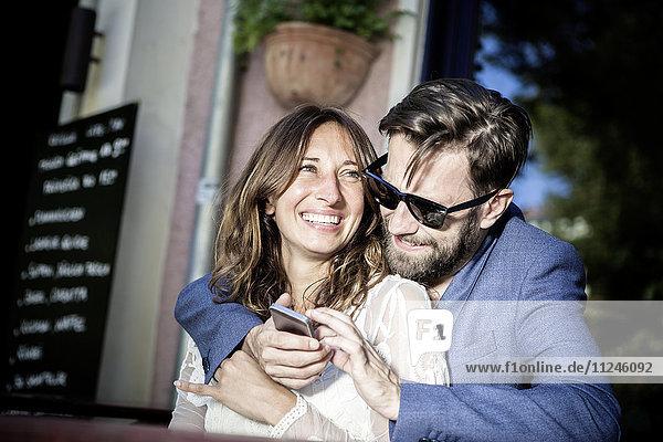 Lächeln und Umarmen zu zweit  mit Smartphone  Berlin  Deutschland